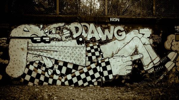 Chien bailloné avec des mains d'homme qui fait un graffiti © Topich