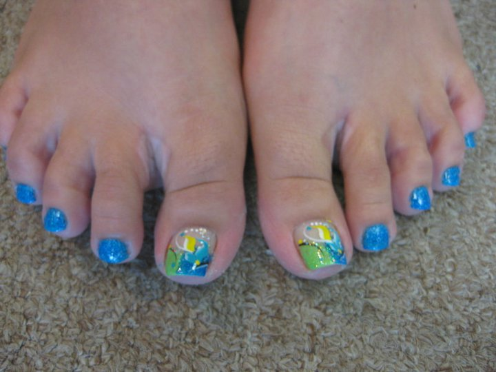 Deep ocean blue/light green tip, light blue flower petals and black swirls topped with yellow petal and white dots.