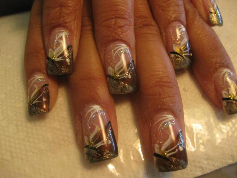 Angled gold sparkled tip topped with angled band of deep copper, white lily petals, white/sparkly swirls and gold dots.