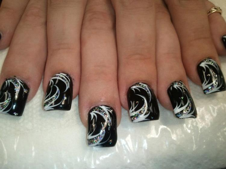 Classy full onyx black nail topped with white and sparkling swirls and sparkle clusters.