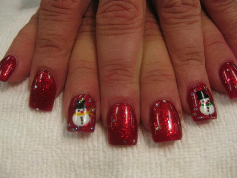 Full sparkling red nail dotted with diamond flecks and snowman with black hat/yellow scarf/red nose and black buttons/eyes.