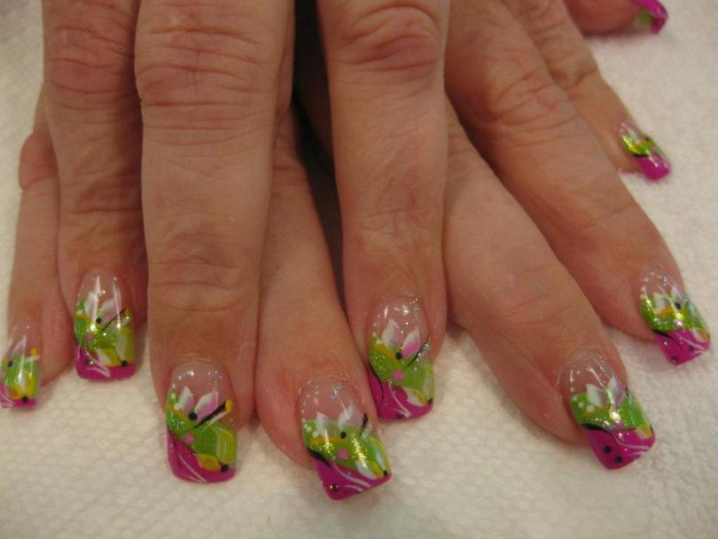 Angled sparkling bright pink tip below angled sparkling bright green band with yellow/pink/white lily petals, white/black swirls, pink/white/black dots.