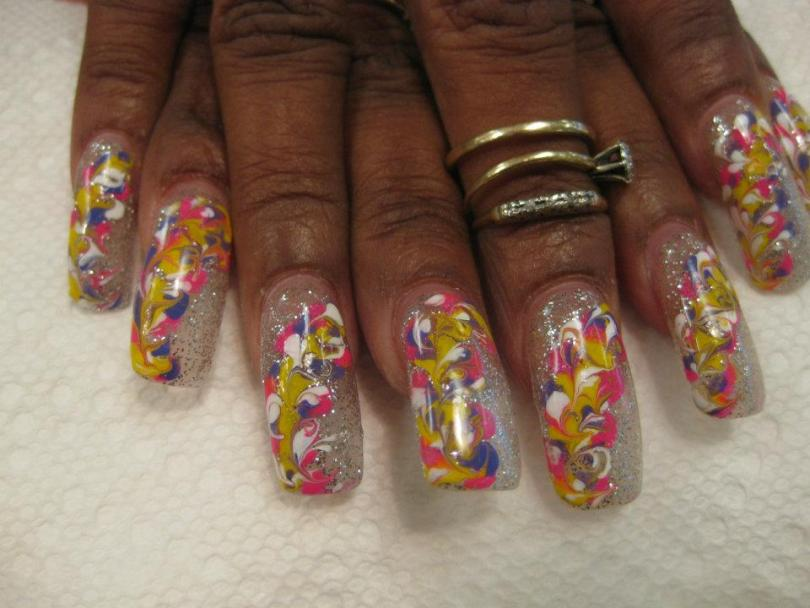 Sparkles on full cloudy nail with yellow/pink/white/blue swirled flower petals.