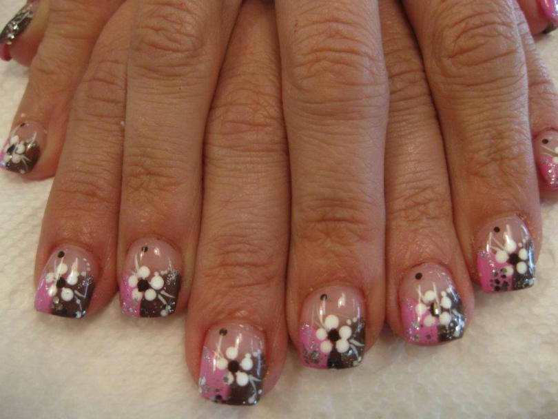 Half sparkling pink/half sparkling chocolate brown tip under five white-petal daisy with black center, white/sparkly swirls.