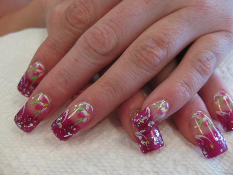 Sparkling pink tip with multiple mirrored glue-ons, pink/white lily petals, green/white/sparkly swirls, white/yellow dots.