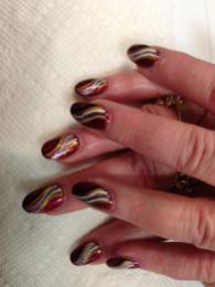 Creamy red full nail with black, sparkly gold, silvery white, sparkly swirls.