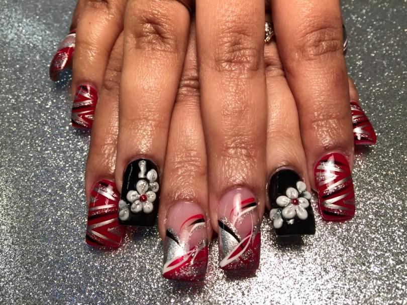 Black nail w/white/silvery sparkled flower/petals, red dot OR Angled red/silver/sparkly tip w/white/red/black swirls OR red nail w/silver/black designs.
