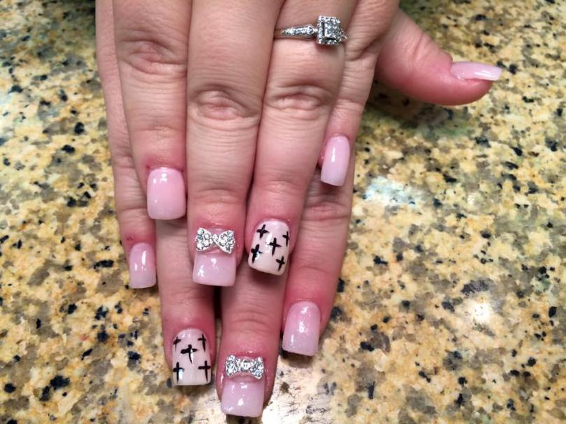 Opaque pink nail, with black crosses OR sparkly/diamond bowtie.