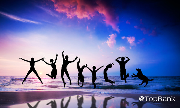 Happy people and dog jumping together on the sunset beach Image
