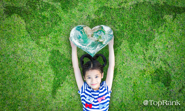 Smiling girl on lawn holding a heart-shaped earth image.
