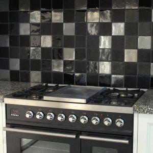 Een spatwand in de keuken met zilver en zwarte tegels