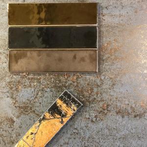 rechthoekige kleine wandtegels in goud, brons of koper.