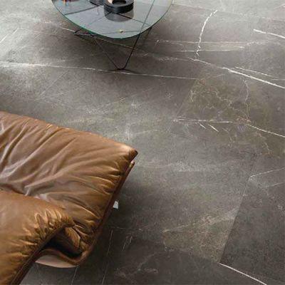 Donker grijze marmerlook tegel met bruine lederen zetel.