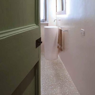 Badkamer met grijze natuursteen granito vloer, witte muren en groene badkamer deur.