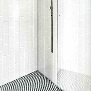 Douche met witte verticaal geplaatste metrotegels.