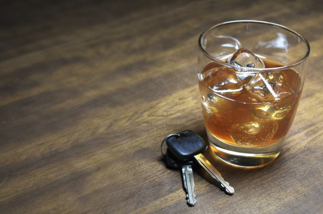 Glass of whiskey and car keys on wooden table.