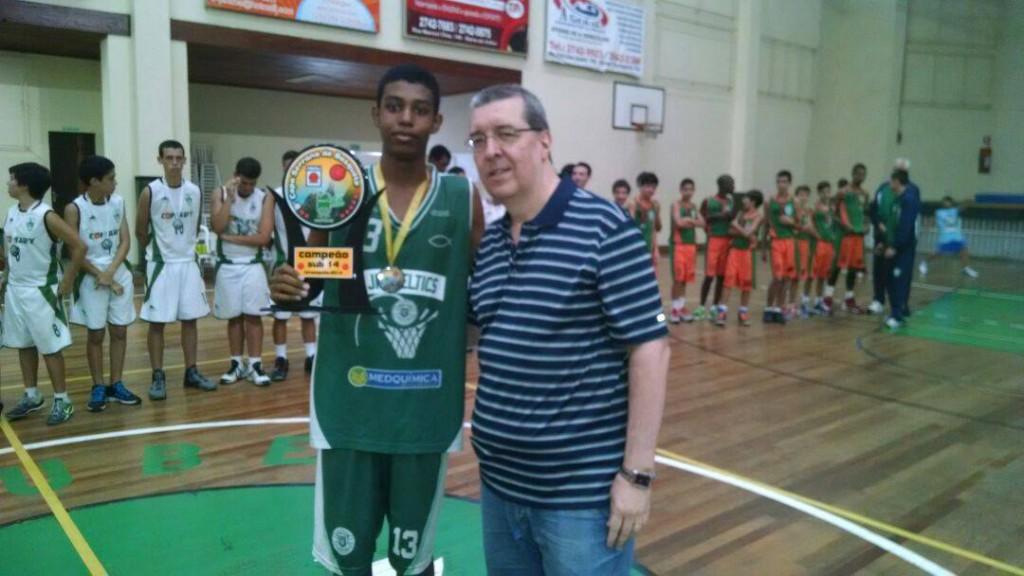 Capitão do JF Celtics, o ala Vitor Gabriel recebe o troféu de campeão das mãos do presidente da FBERJ, Álvaro Lionides. Foto: Alexandre Willians