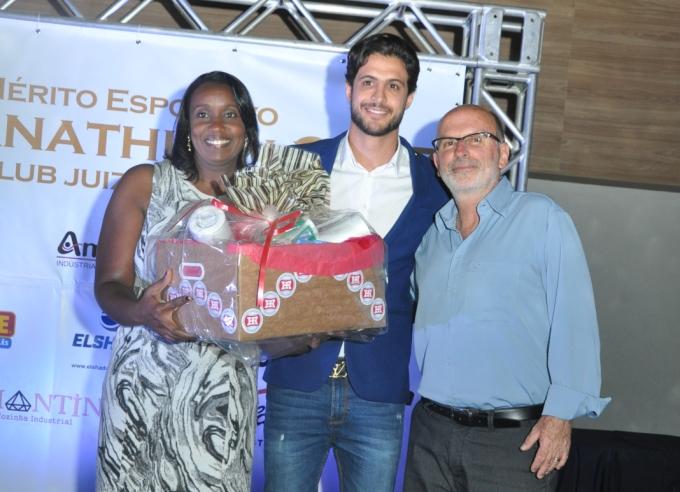 Hudson recebe uma cesta com produtos da Hiperroll Embalagens, entregue pela diretora de Marketing da Hiperroll, Vanessa Silveira, e presidente do Conselho Municipal de desportos, Antônio Pereira de Carvalho Filho