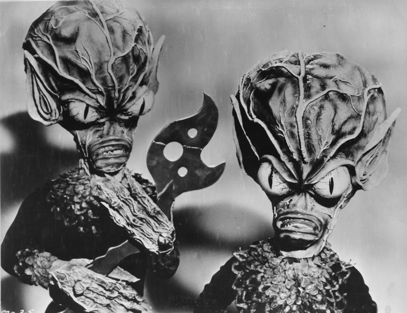 Invasion of the Saucer Men, 1957, motion picture, AIP.  A publicity photo of the Saucer Men.  The actor on the left holds a tool fashioned by Paul Blaisdell out of balsa wood and painted to look like metal.  Blaisdell cautioned the cast that the prop was extremely fragile, but one of them managed to break it anyway.  The tool never appeared in the finished film because of the mishap, but is preserved here in this photograph, with the hastily repaired break clearly visible. Click to enlarge.