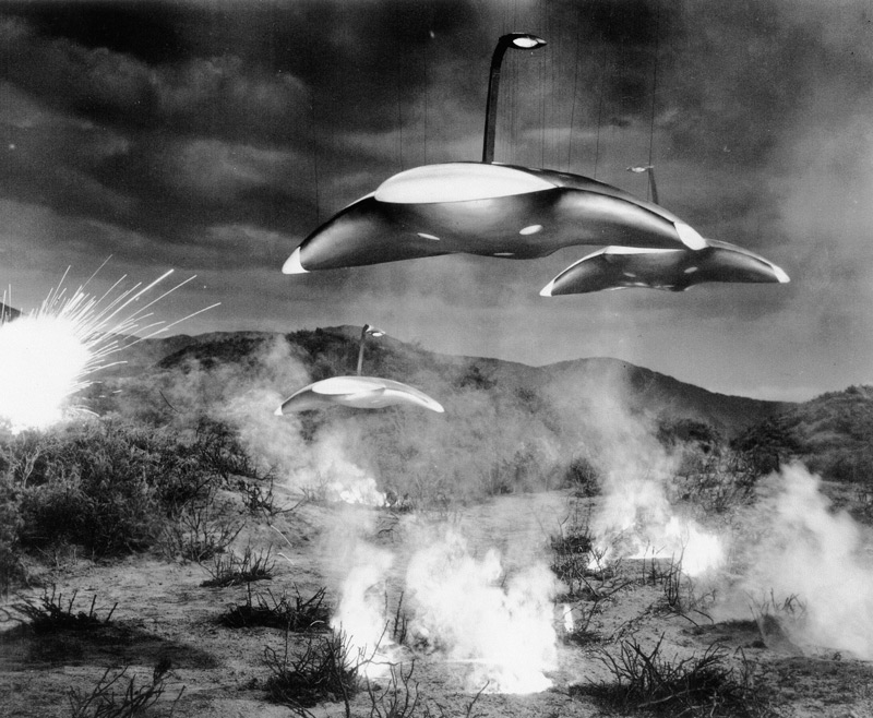 From the gully where the meteor crashed to earth in the film version of The War of the Worlds, three sleek alien ships emerge.  The ships were actually 42 inches in diameter and were suspended by wires like marionettes above a miniature set on Stage 18 at Paramount Studios.  Through the use of trick photography they were made to appear 30 feet wide and suspended from the ground on nearly invisible beams. The beam effect substituted for the articulated mechanical legs of the Martian tripods as they were described in Wells' original 1897 novel. Click to enlarge.
