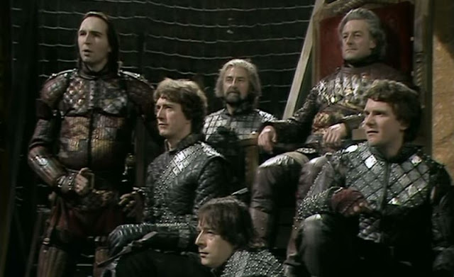 Mark Wing-Davey as the valiant armored Warwick (left) with York (enthroned) and his three sons, from the Jane Howell production, BBC Shakespeare Collection.