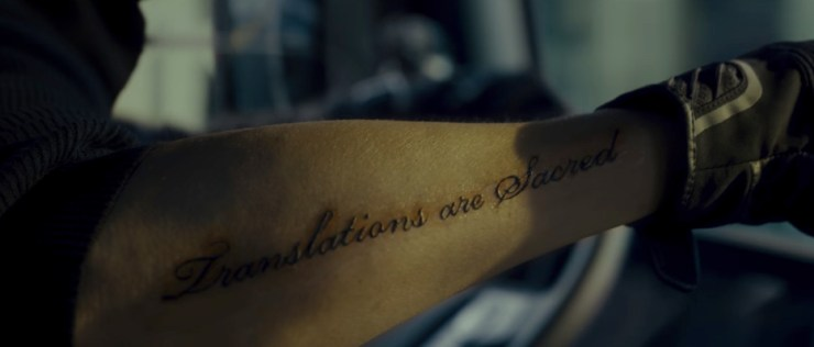 """Afreshly tattooed forearm showing raised black script reading """"Translations are Sacred."""" From the movie Okja."""