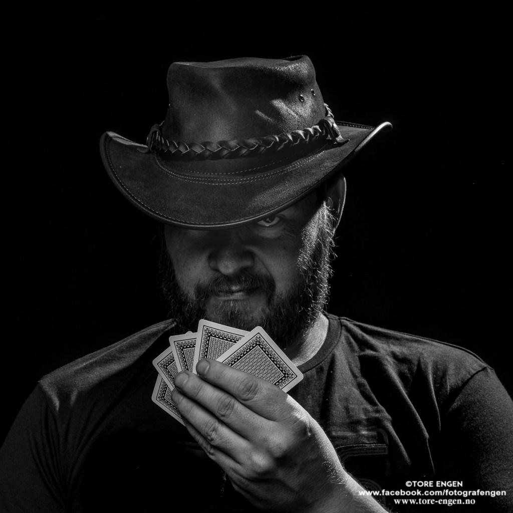 Svart hvitt portrett av mann med skjegg og hatt som holder 5 spillkort