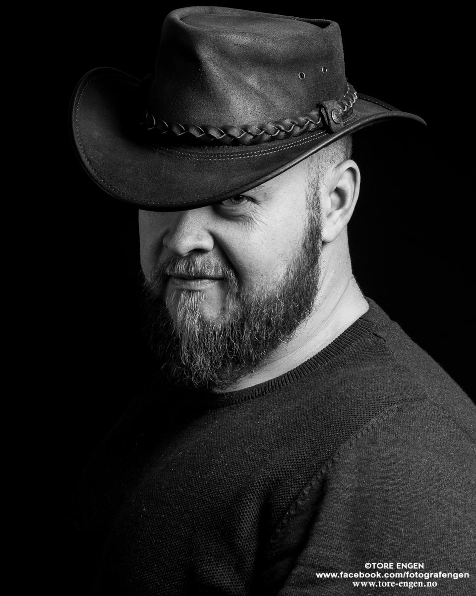 Selvportrett av Tore Engen med skjegg og hatt i svart-hvitt