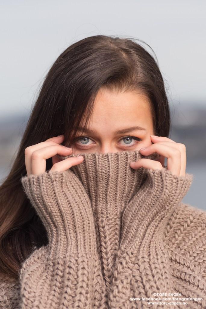Portrett av kvinnelig fotomodell som har trukket genseren oppunder øynene