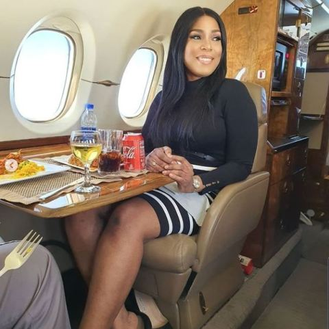 Linda Ikeji and father posing inside a private jet