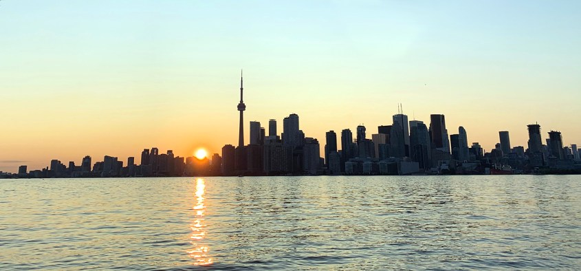 View of downtown Toronto from Toronto Island Park. Sun setting to the west of the CN Tower.