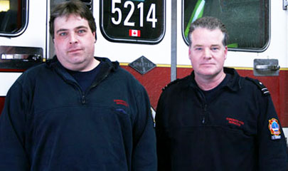 Barry Todhunter and Rob Bygrave stand in front of their station's fire truck.