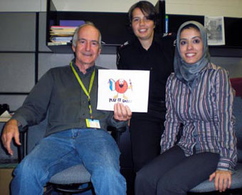 Vern Kennedy, along with Liliana Dos Santos and a Centennial College volunteer, holds up the Play It Smart logo in his office.