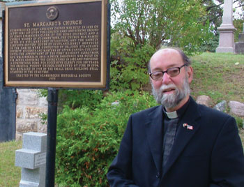 Father Ron Scott poses with the commemorative plaque outside St. Margaret's in-the-Pines Anglican Church. The parish turns 175 this year.