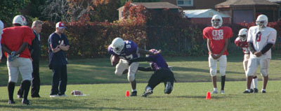 Members of West Hill's junior football team participate in a tackling drill at practice.