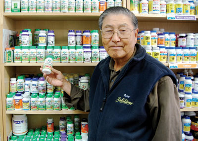 Cutline: Ken Park, owner of Morningside Health Foods, showcases a bottle of Echinacea, a popular natural alternative to the flu shot.