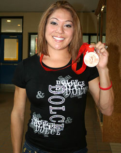 Priscilla Lopes-Schliep shows off her medal at Pope John Paul II Catholic Secondary School, where she was once a star track athlete.