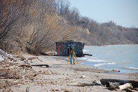 A beach surveyor stands in front of a piece of concrete, which  has graffiti on it. (Selena Mann/Toronto Observer)