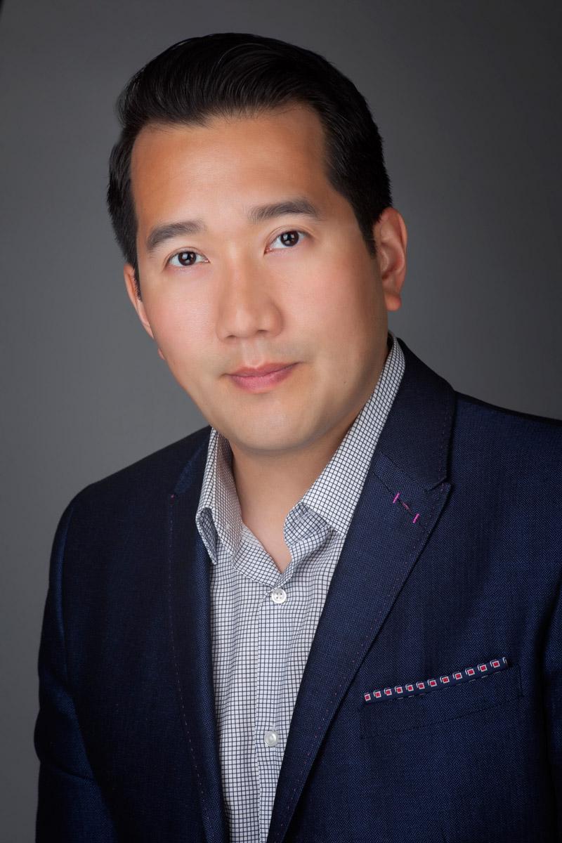 LinkedIn portrait of man against a grey background in studio