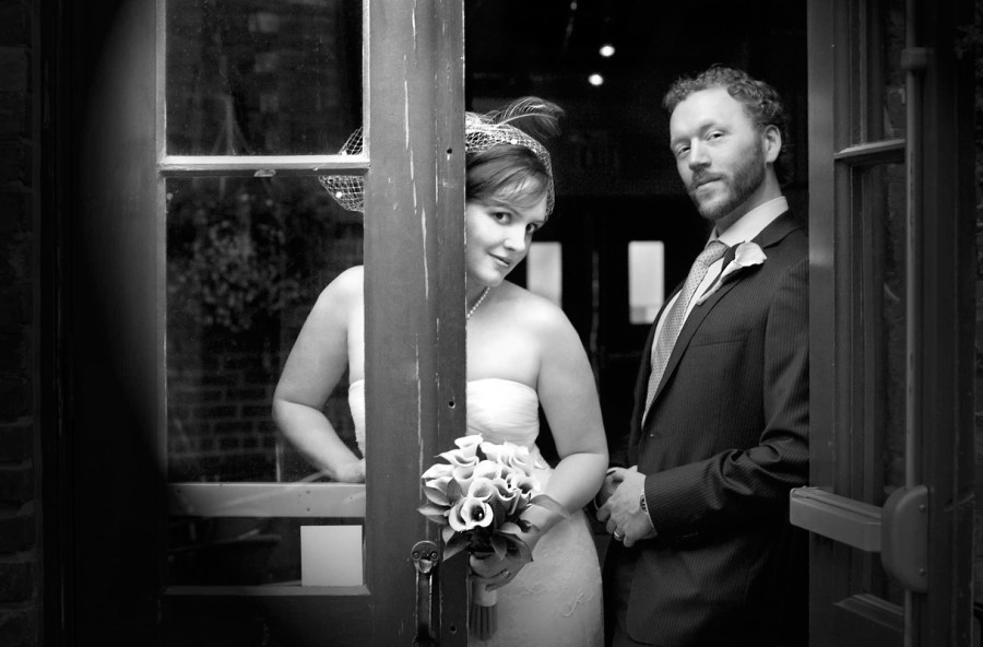 Bride and groom in black and white leaning on doorway