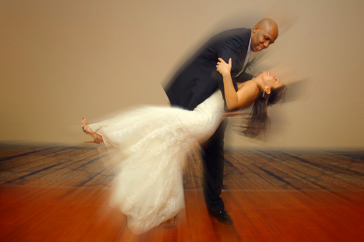 Groom bending over bride to give her a kiss with motion effect