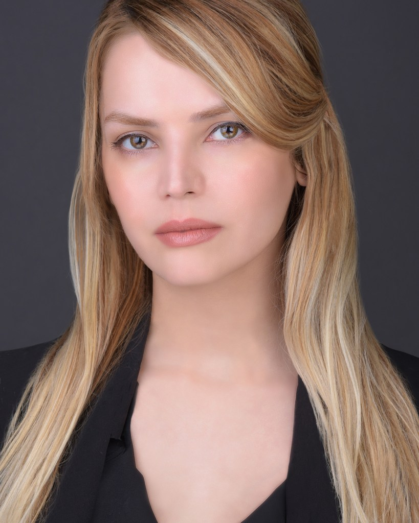 Female headshot of blonde looking directly at camera with grey background.
