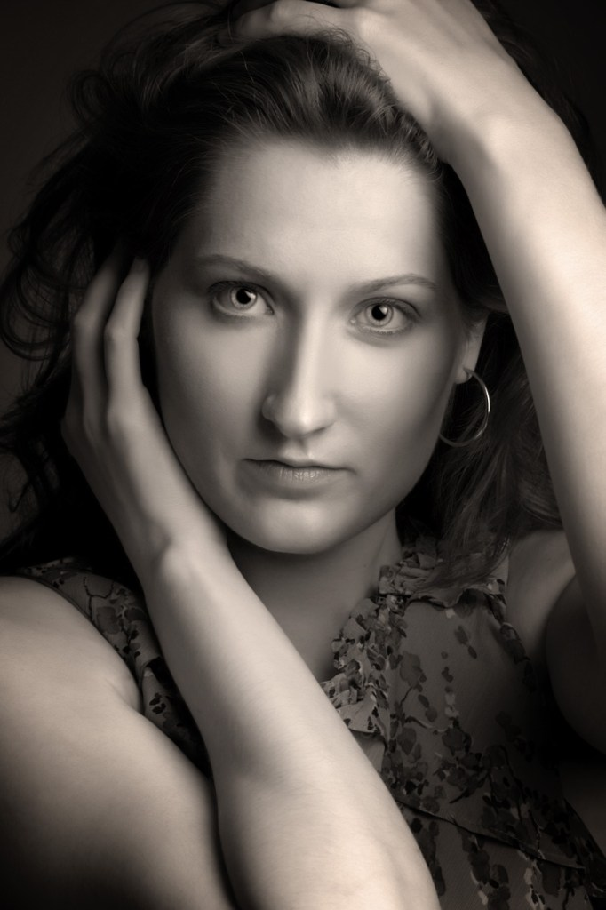Fashion headshot in sepia tone of female with hands on head and cheek