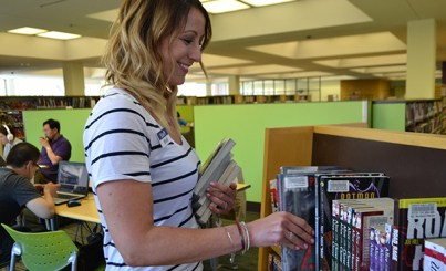 women putting books on shelve in library