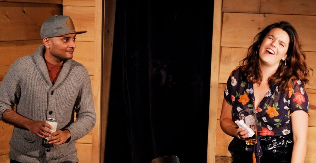 A photo of Zohaib Khan and Cydney Connell standing on stage sharing a laugh at a live version of Sketch in 60 at Bad Dog Theatre