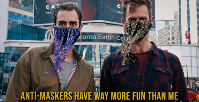 """Andrew and Tyson stand next to each other facing the camera in Yonge-Dundas Square with the Toronto Eaton Centre in the background. Andrew wears a black face with long purple sequin fringes. Tyson wears a black masks with long gold sequin fringes. At the bottom is yellow text that reads """"Anti-Maskers Have Way More Fun Than Me"""""""