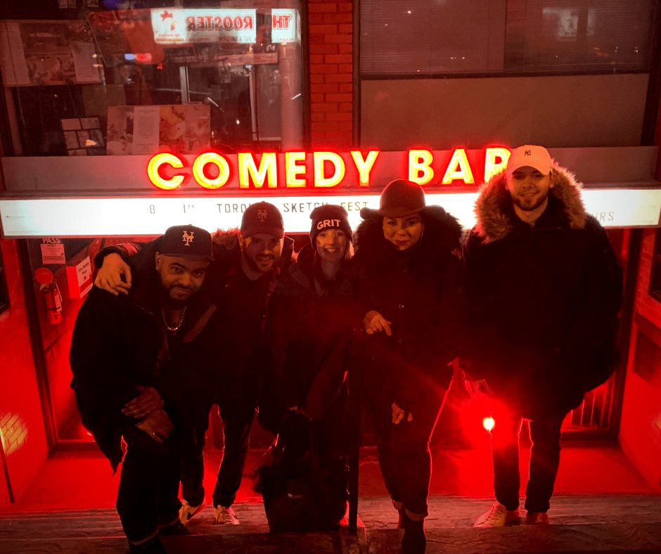 Five comedians in winter clothing posing in front of the Comedy Bar entrance, smiling for the camera.