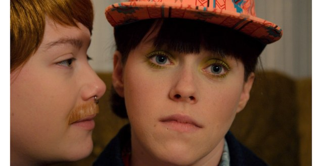 A close up image of two faces. Elena Eli Belyea is on the first side looking past the camera. Sydney Campbell looks directly at Elena from the side, wearing a fake moustache.
