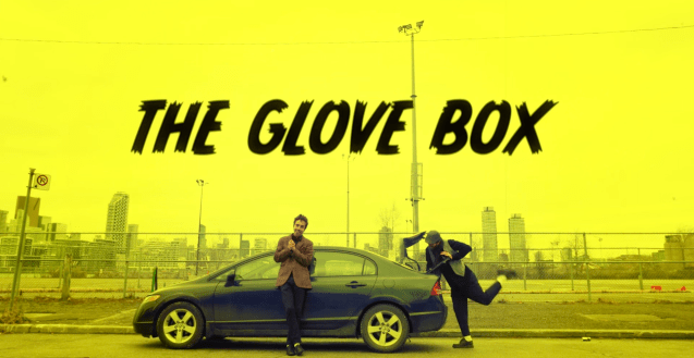 "A yellow title card that reads ""The Glove Box"" with Chase Jeffels standing, facing the camera, in a cityscape by a car and Joel Jeffels packing the truck of the car."
