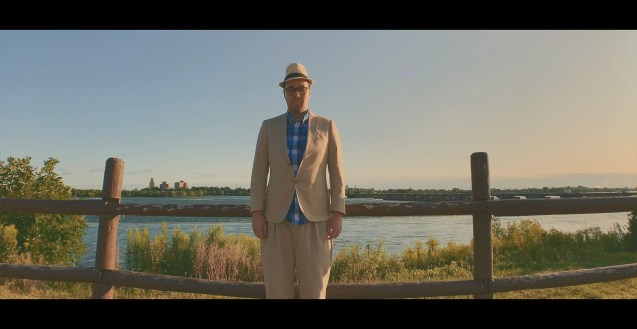 Desmond stands with his arms at his side, in front of a wooded fence, in front of a body of water. He wears a light coloured suit, a blue checkered shirt, a hat and glasses.